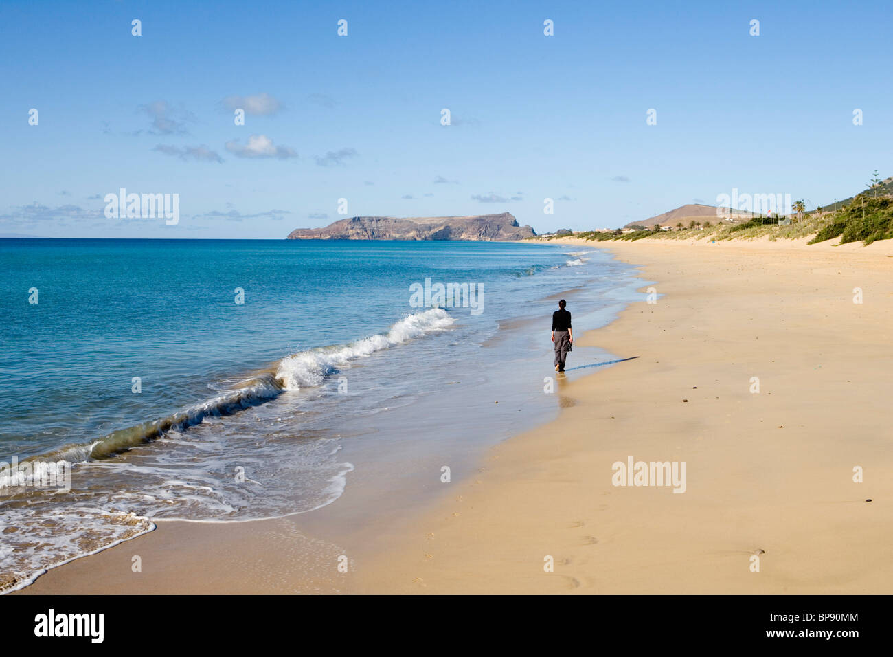 Woman strolling along Porto Santo Beach, Porto Santo, near Madeira, Portugal - Stock Image