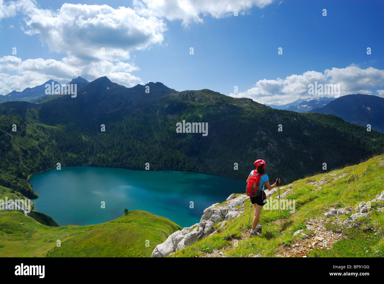 Woman hiking above reservoir Lago Ritom, Ticino Alps, Canto of Ticino, Switzerland Stock Photo