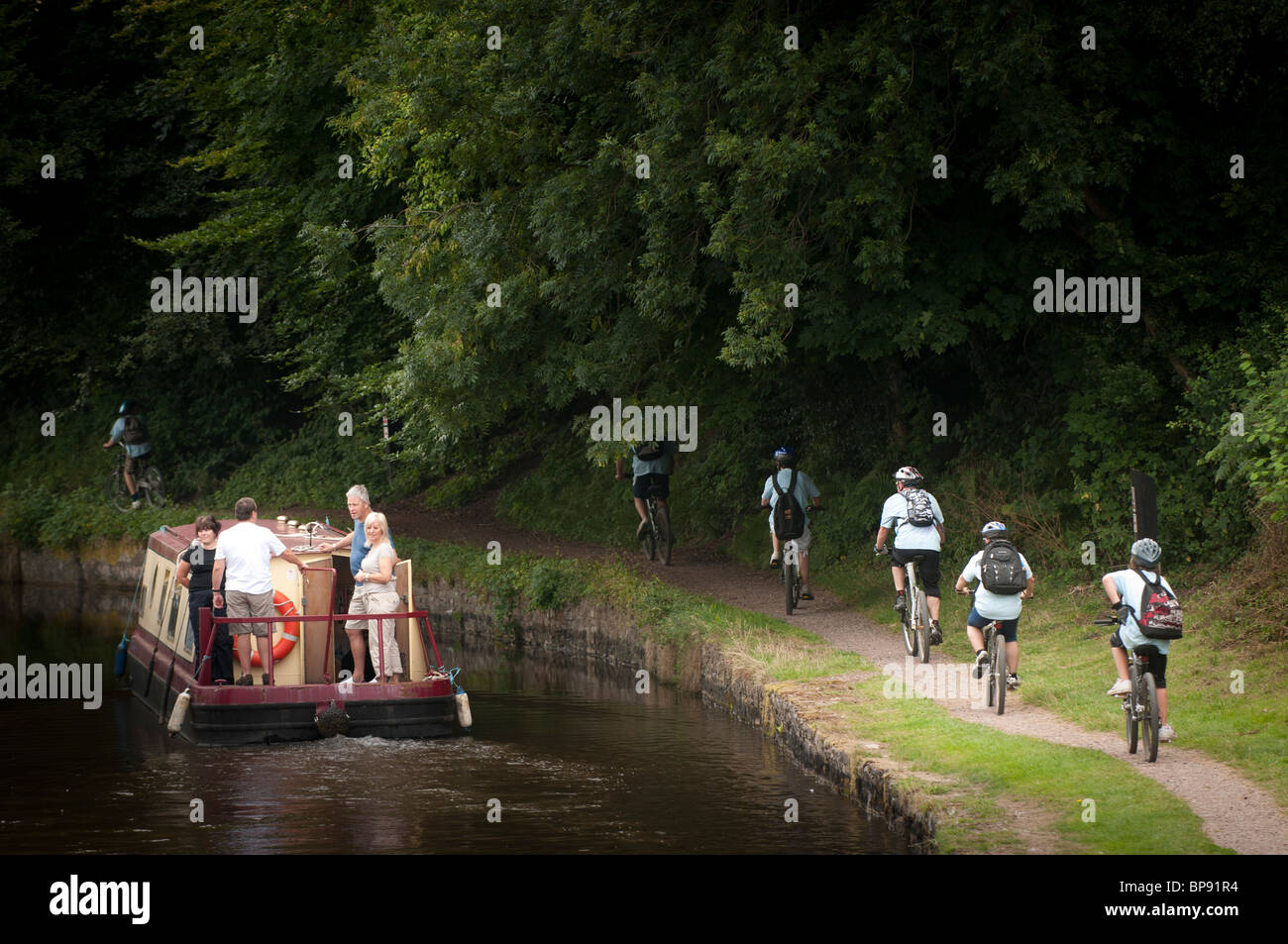Cyclists on the towpath and a narrowboat on the Monmouthshire and Brecon Canal, South Wales UK - Stock Image