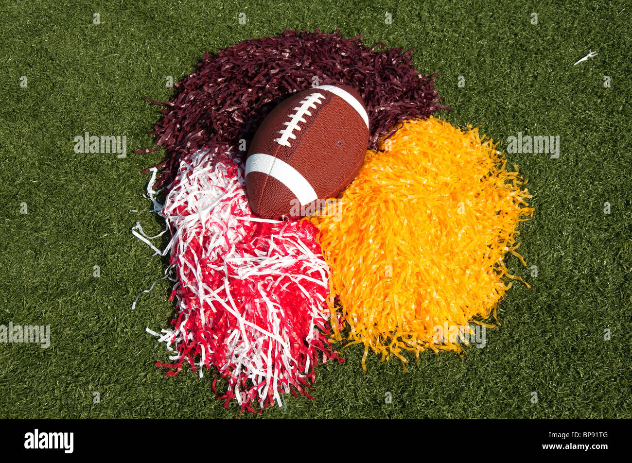 American football and pom poms on field. - Stock Image
