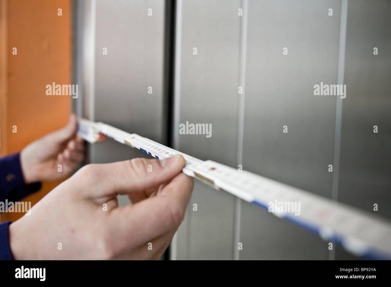 Hands holding yardstick, Munich, Bavaria, Germany - Stock Image