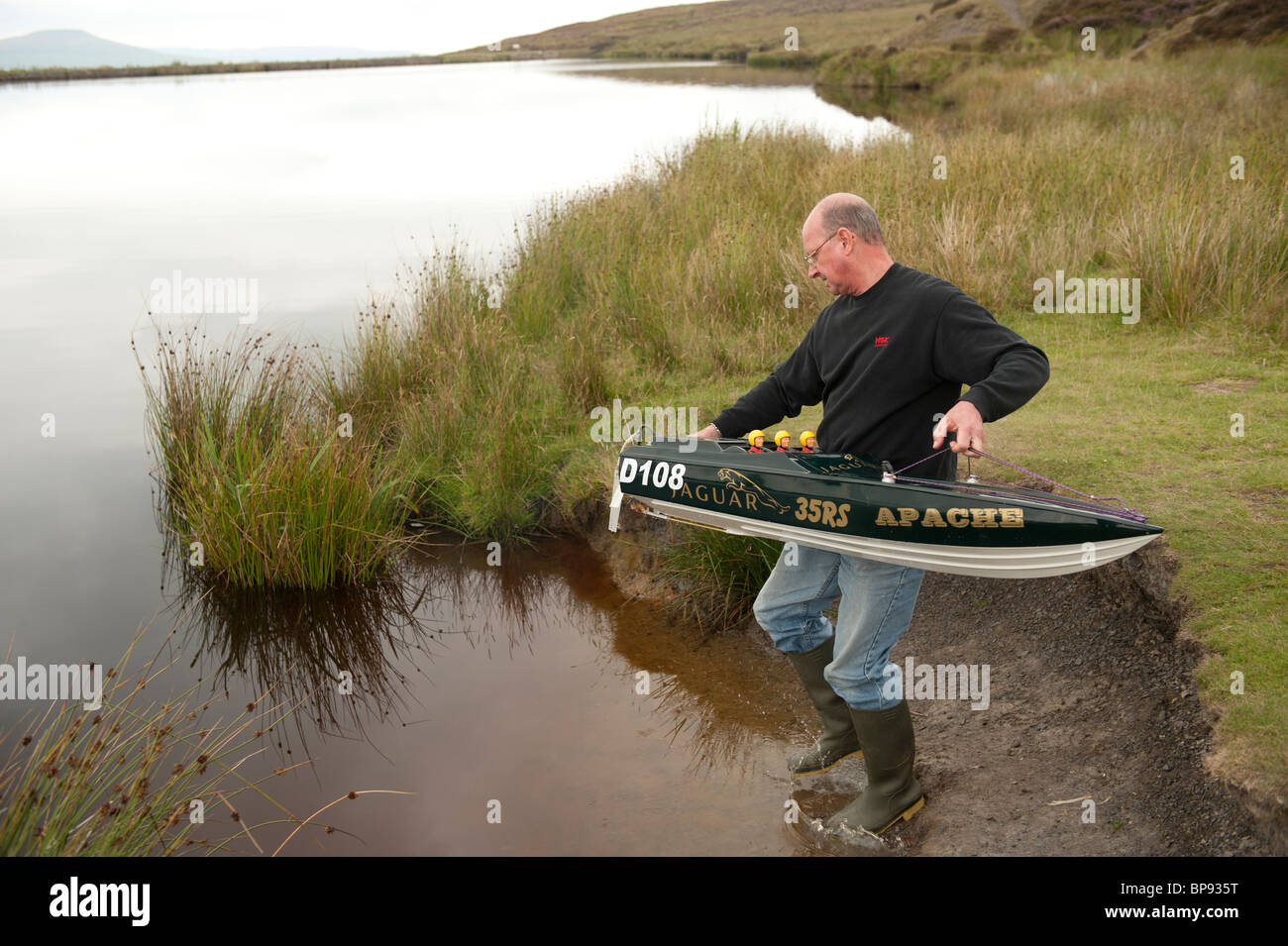 Men racing with radio - controlled model power boats on a pond, Wales UK - Stock Image