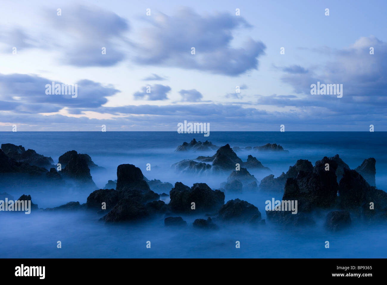 Lava rocks at dusk surrounded by sea water, Porto Moniz, Madeira, Portugal - Stock Image