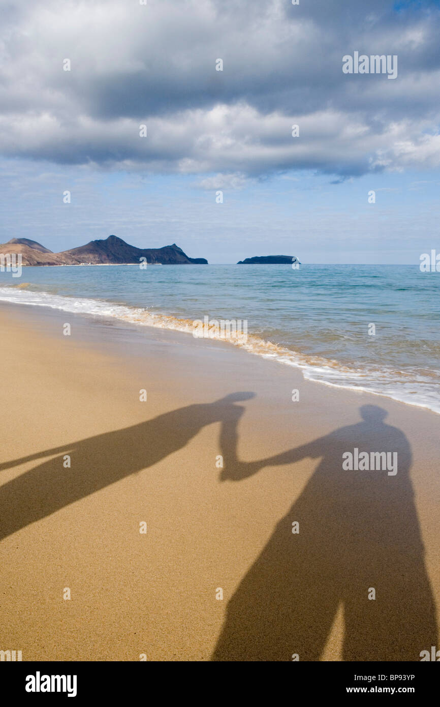 I Wanna Hold Your Hand, Shadow of couple holding hands on the beach, Porto Santo, near Madeira, Portugal - Stock Image