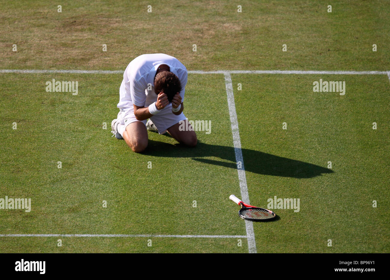 A devastated Nicolas Mahut of France kneels on the ground after his defeat at Wimbledon 2010, - Stock Image