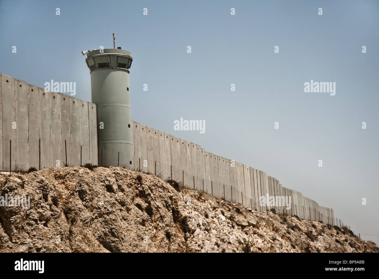 The Israeli separation wall cuts through Palestinian land near the West Bank town of Kalandia. - Stock Image