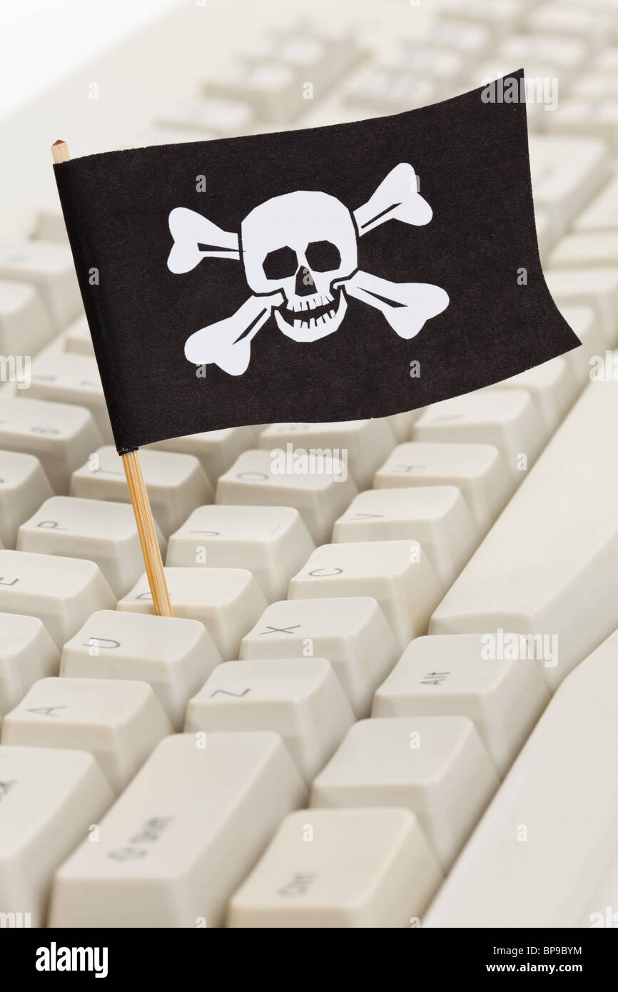 Pirate Flag and Computer Keyboard, concept of Computer Hacker - Stock Image