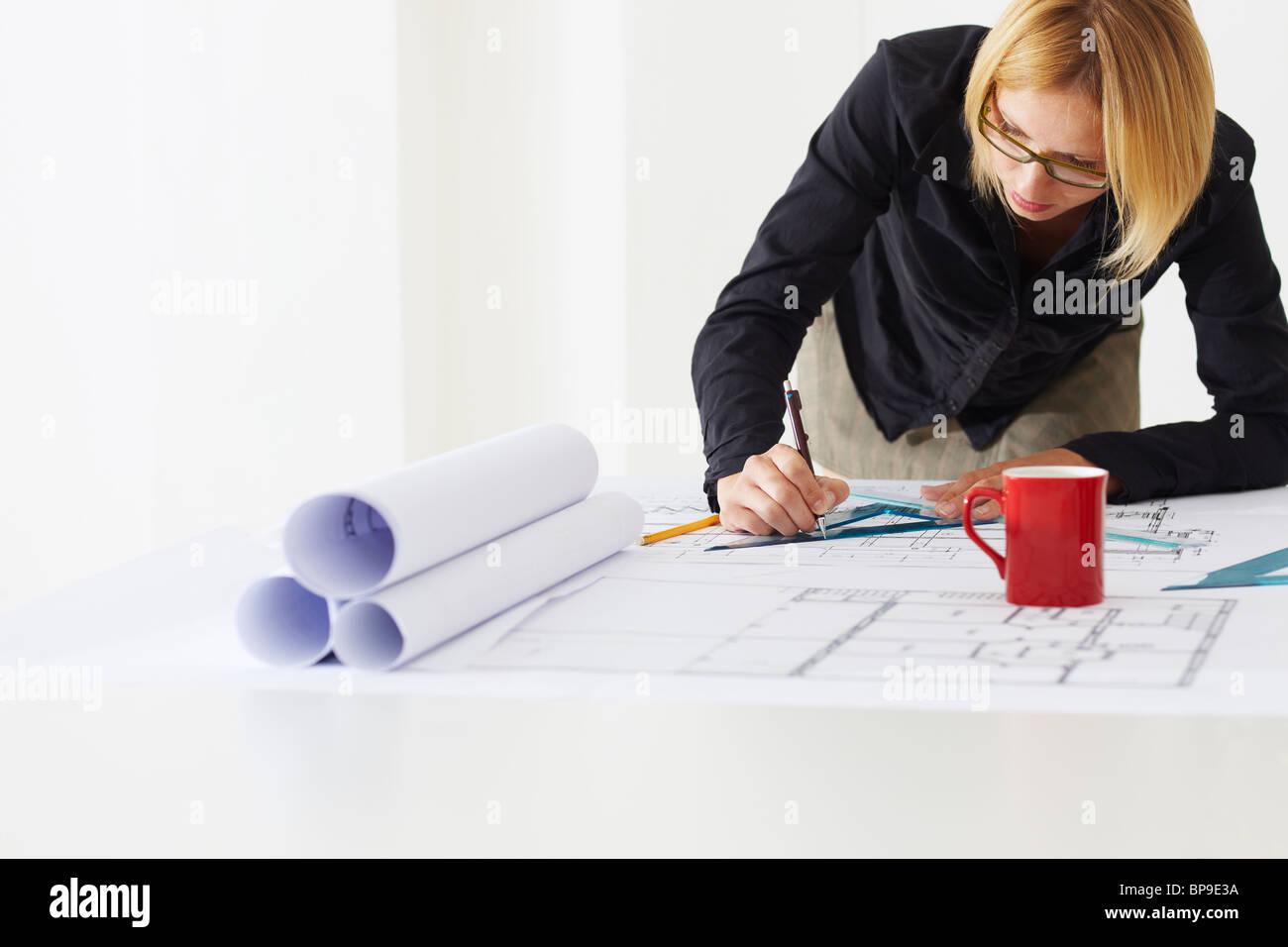 female architect drawing on blueprint - Stock Image