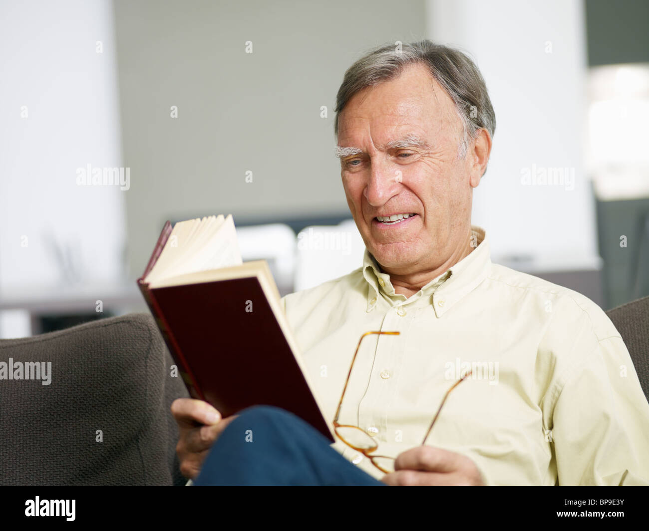 senior man reading book at home. Copy space - Stock Image