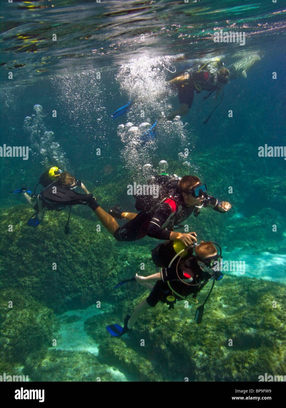 A scuba diving instructor is helping a child with his gear under water. The Blue Lagoon near Cape Greco, Cyprus, - Stock Image