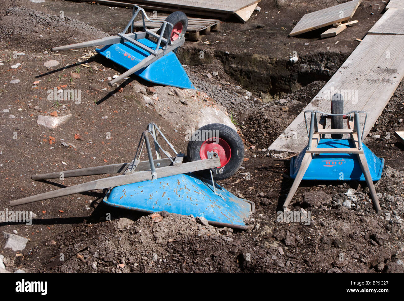 Three blue wheelbarrows at an archeological excavation ground. - Stock Image