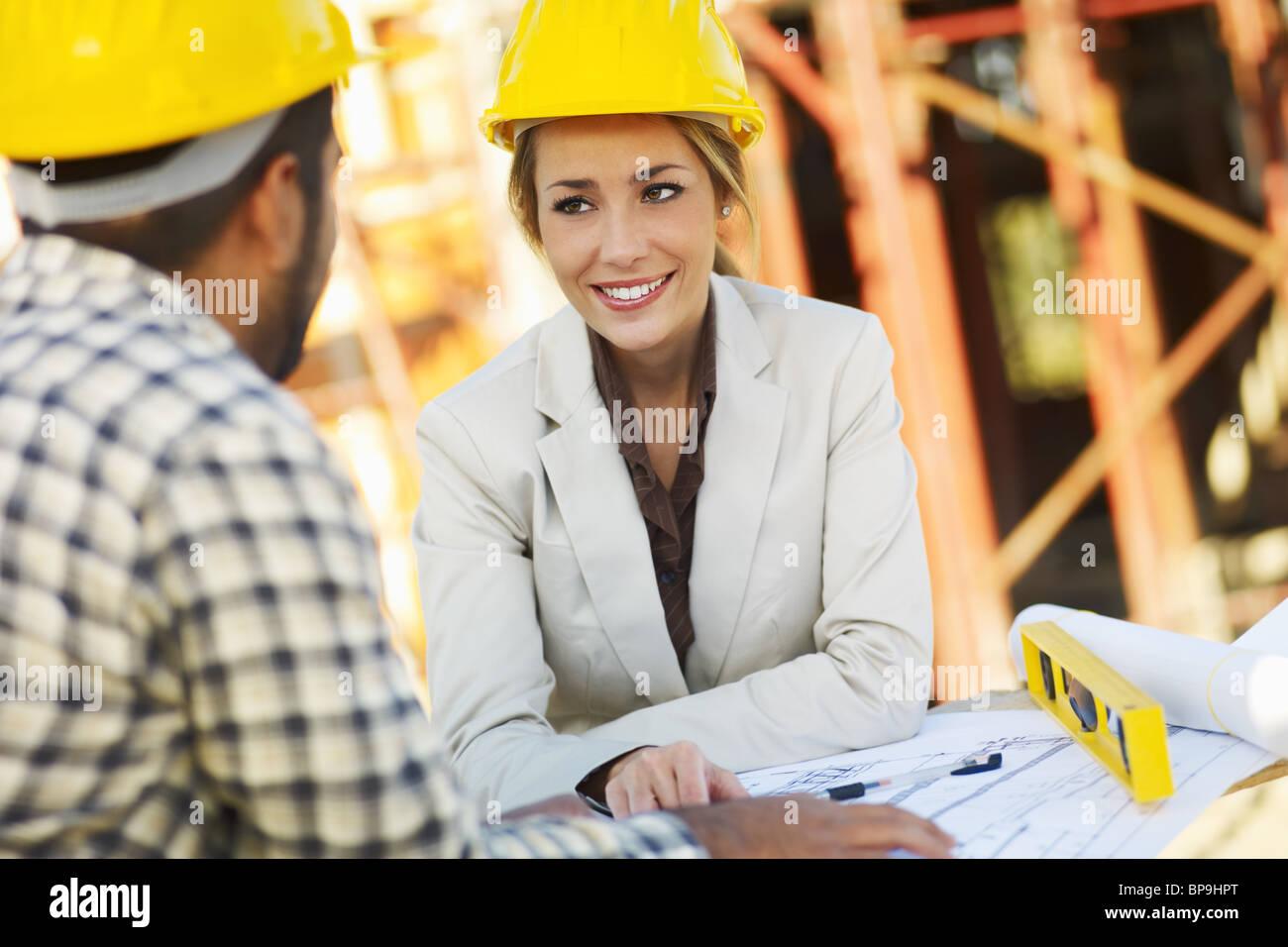 latin construction worker and female architect - Stock Image
