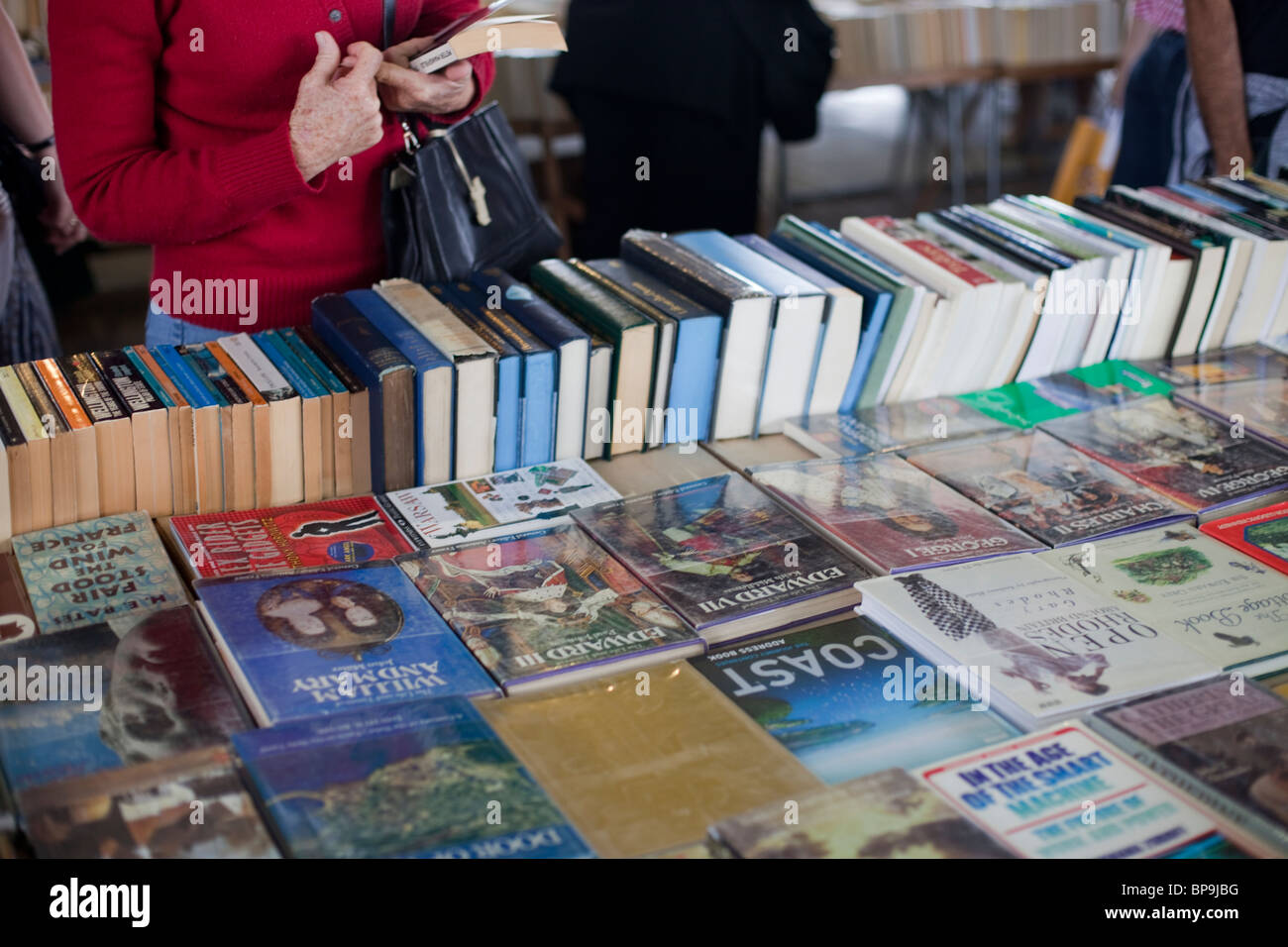 A lady browses a stall selling second hand books on the South Bank of the Thames, London. - Stock Image