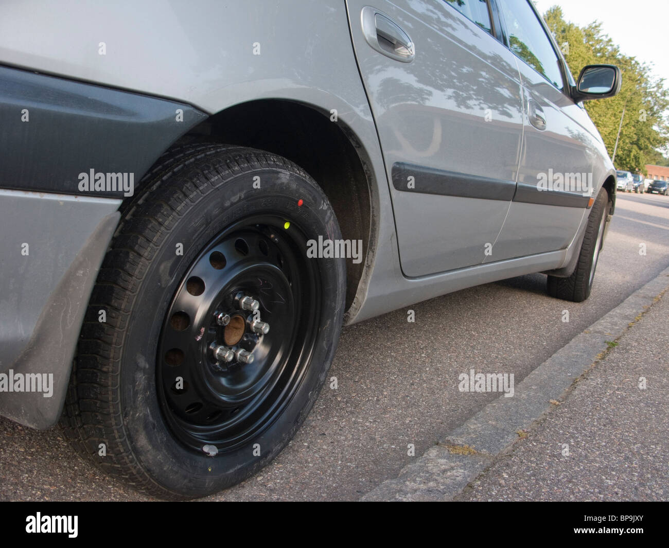The spare tyre has been put on a car that has had a puncture on its rear right wheel. - Stock Image