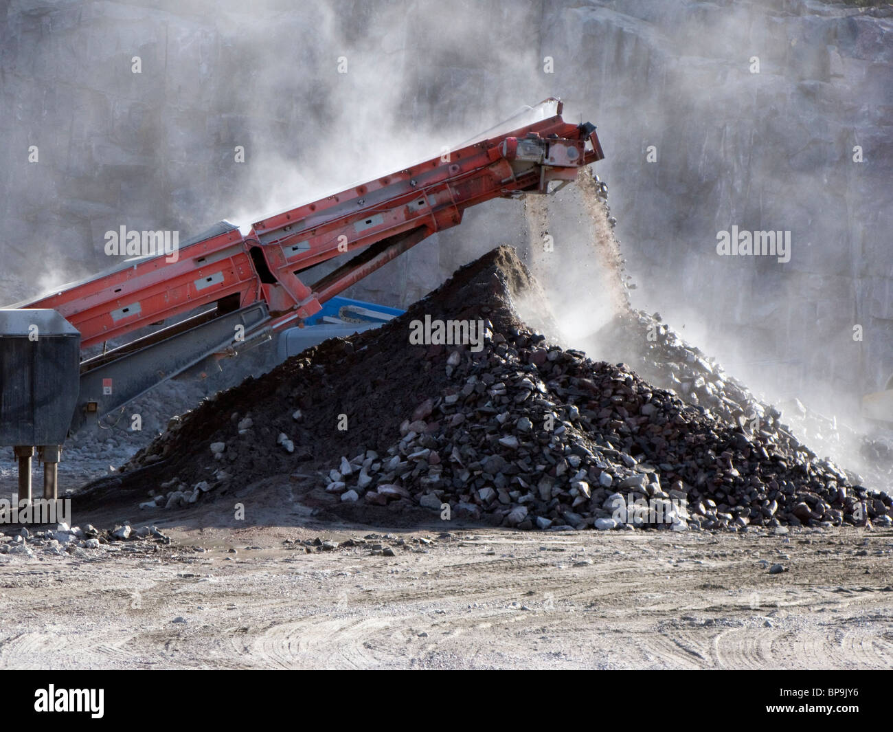 Crushed stones piling up below a conveyor belt from a stone crusher. - Stock Image