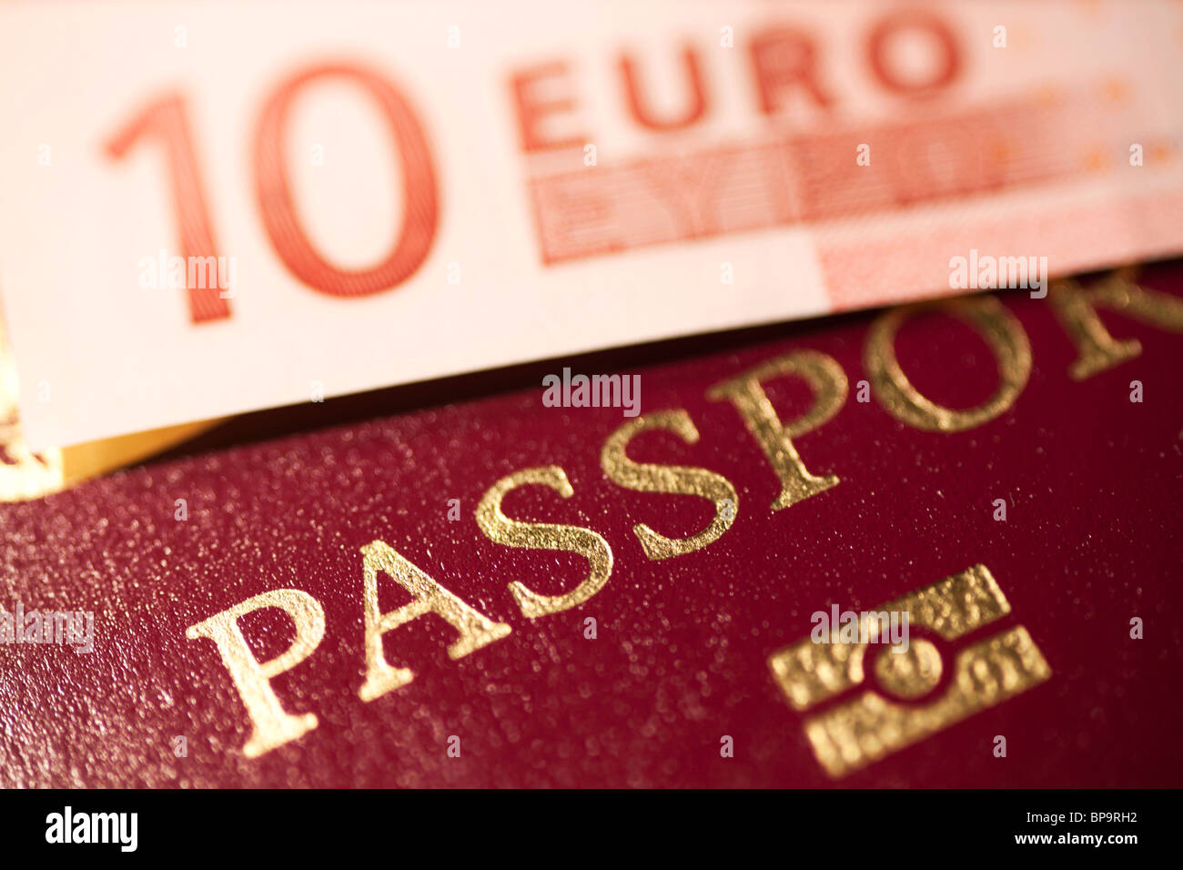 Passport with a 10 euro note on top - Stock Image