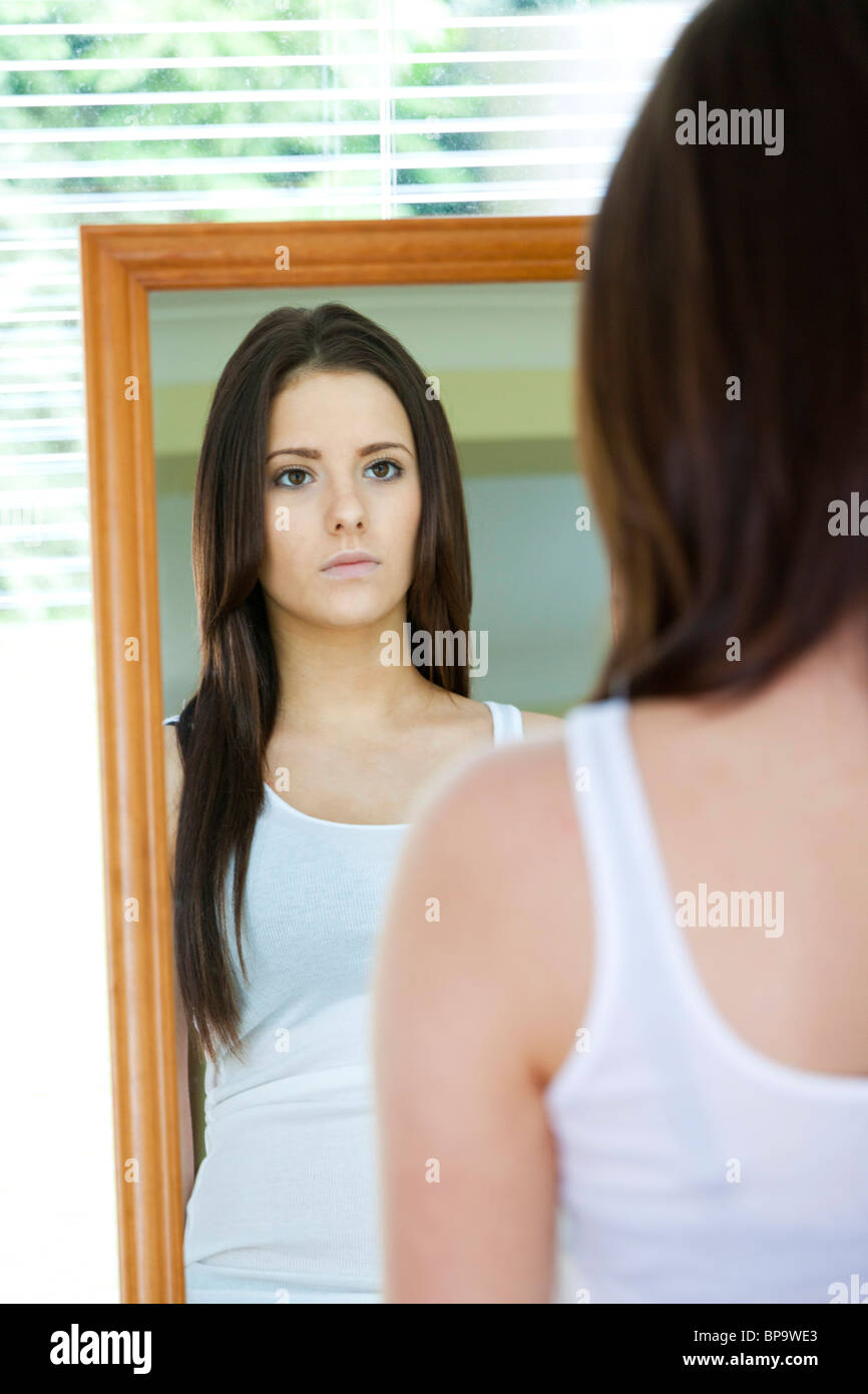 teenage girl looking in mirror - Stock Image