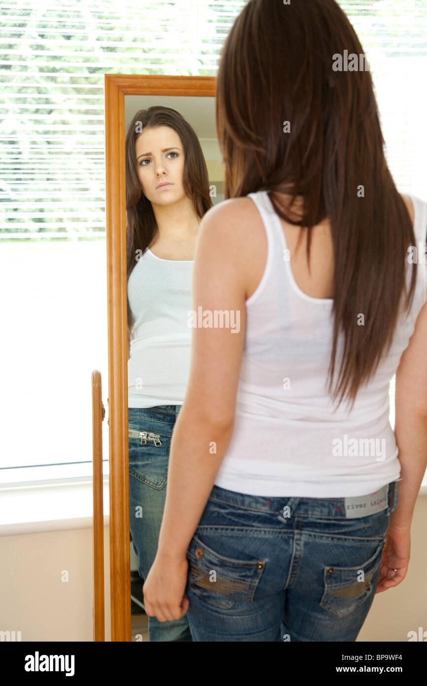teenage girl looking in mirror - Stock Image