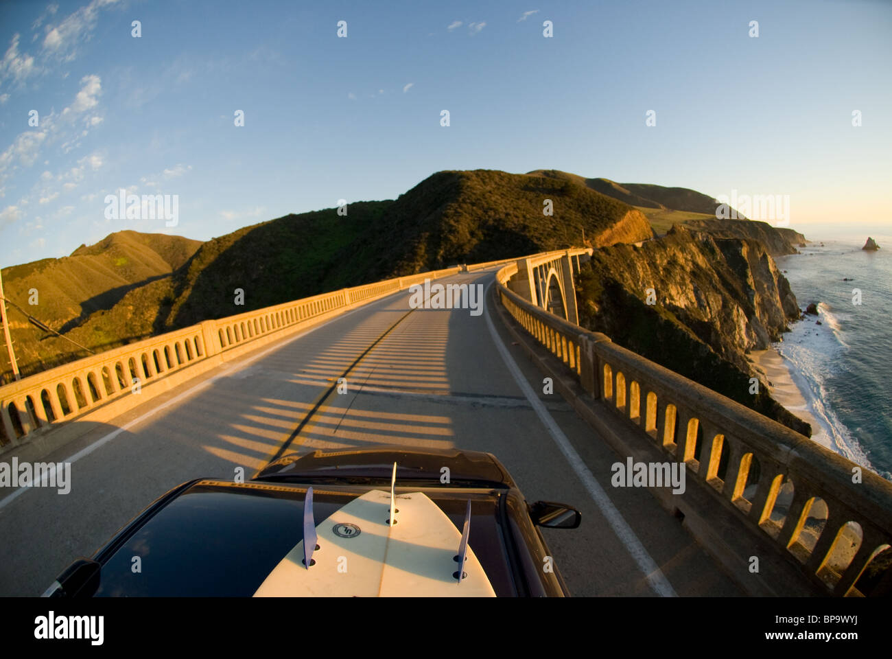 A car with a surfboard on top traveling over the Bixby Creek Bridge, on Highway 1 in Big Sur, California, USA. - Stock Image