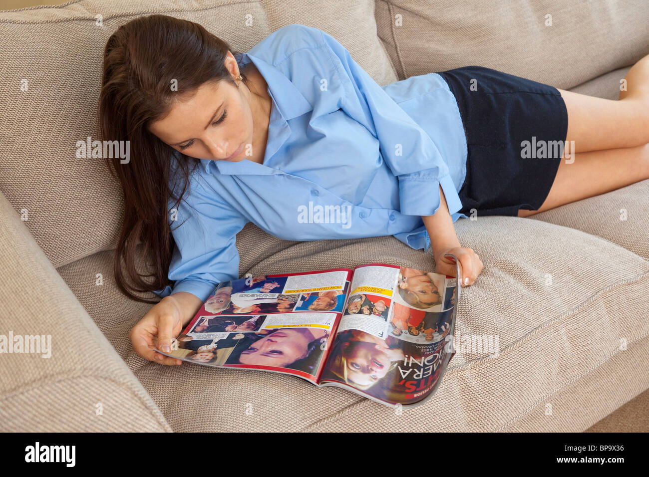 young teenage girl looking at womens lifestyle / celebrity magazine - Stock Image