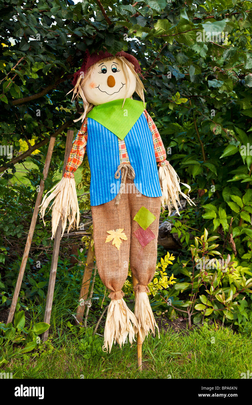 A stuffed scarecrow on a stick under a bush - Stock Image