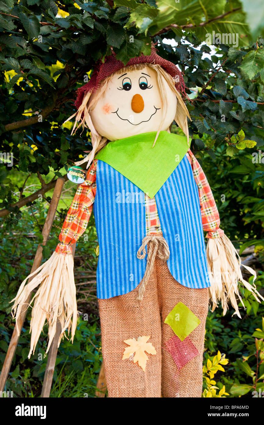 A stuffed scarecrow on a stick under a bush - Stock Image