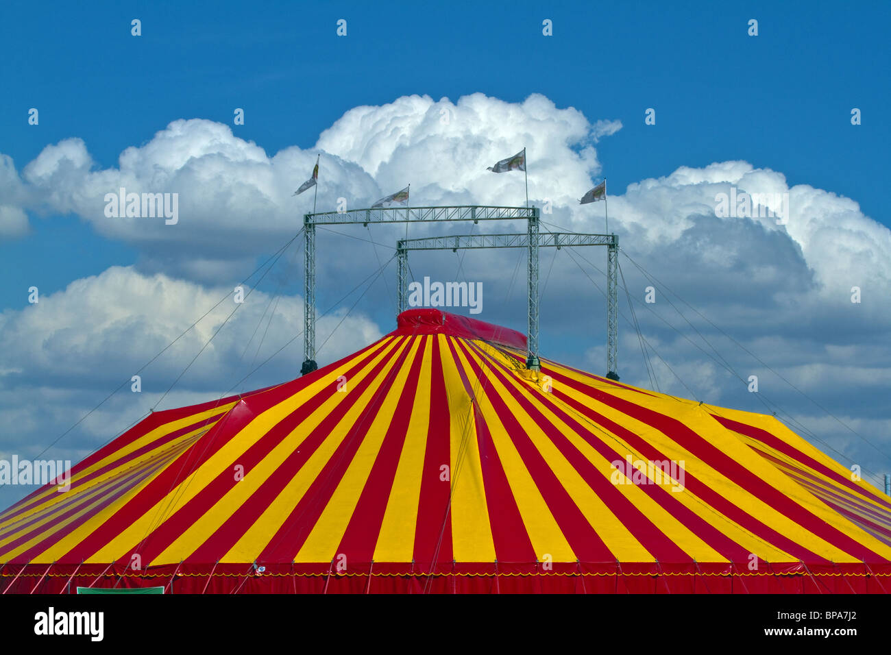 Striped circus tent against a blue sky with fluffy clouds. Horizontal - Stock Image