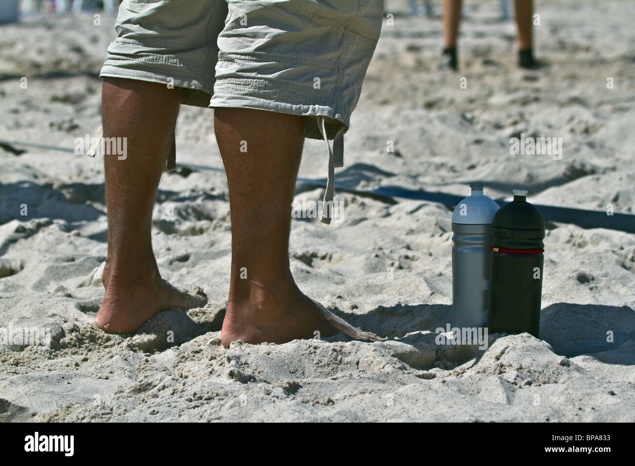 Aarhus, Denmark 2010. Beachvolley National Championship. Close-up feet of Spectator ready to assist with water bottles. - Stock Image
