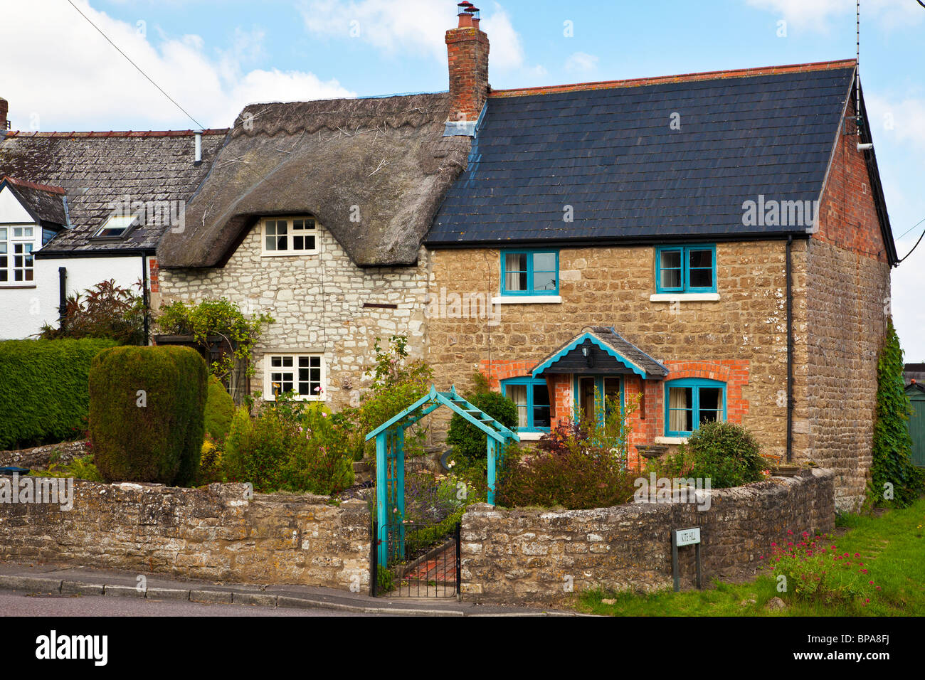 Two typical English stone cottages, one with tiled roof and one thatched. - Stock Image