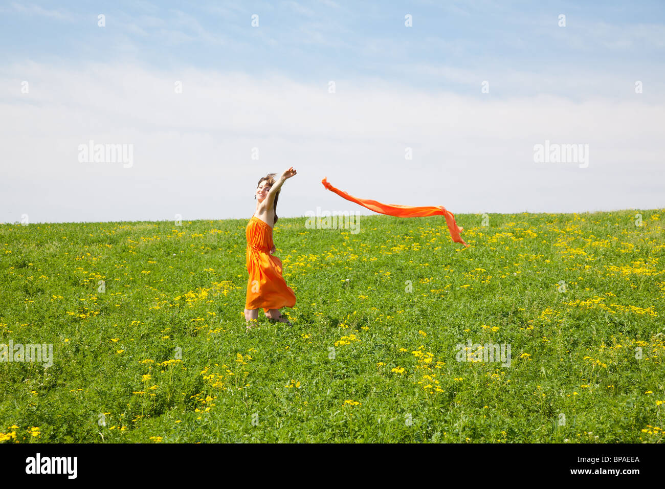 Young woman wearing an orange dress outdoor on a spring day Stock Photo