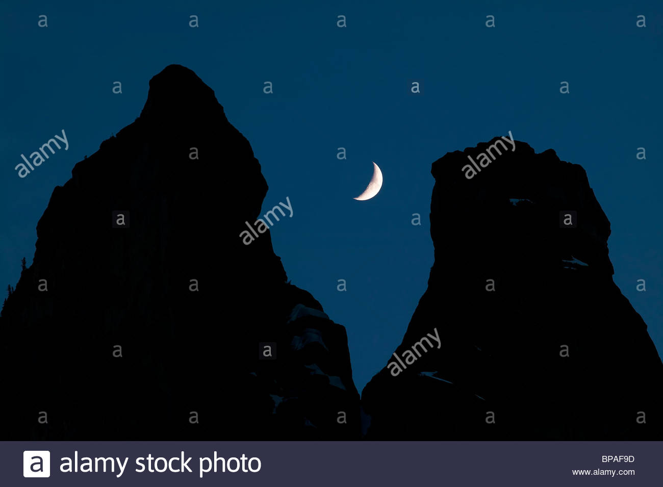 The Early Winters Spires, located in Washington's North Cascades, frame a crescent moon. - Stock Image