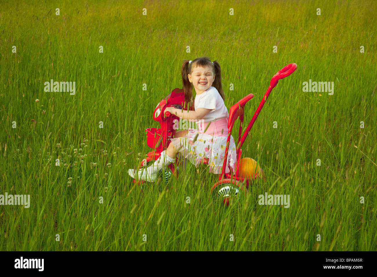 The comical child goes across the field on a bicycle and grimace Stock Photo