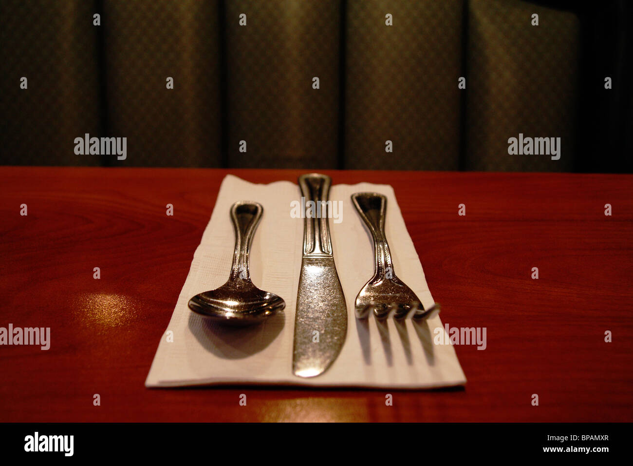 napkin with spoon, knife & fork on coffee shop table - Stock Image