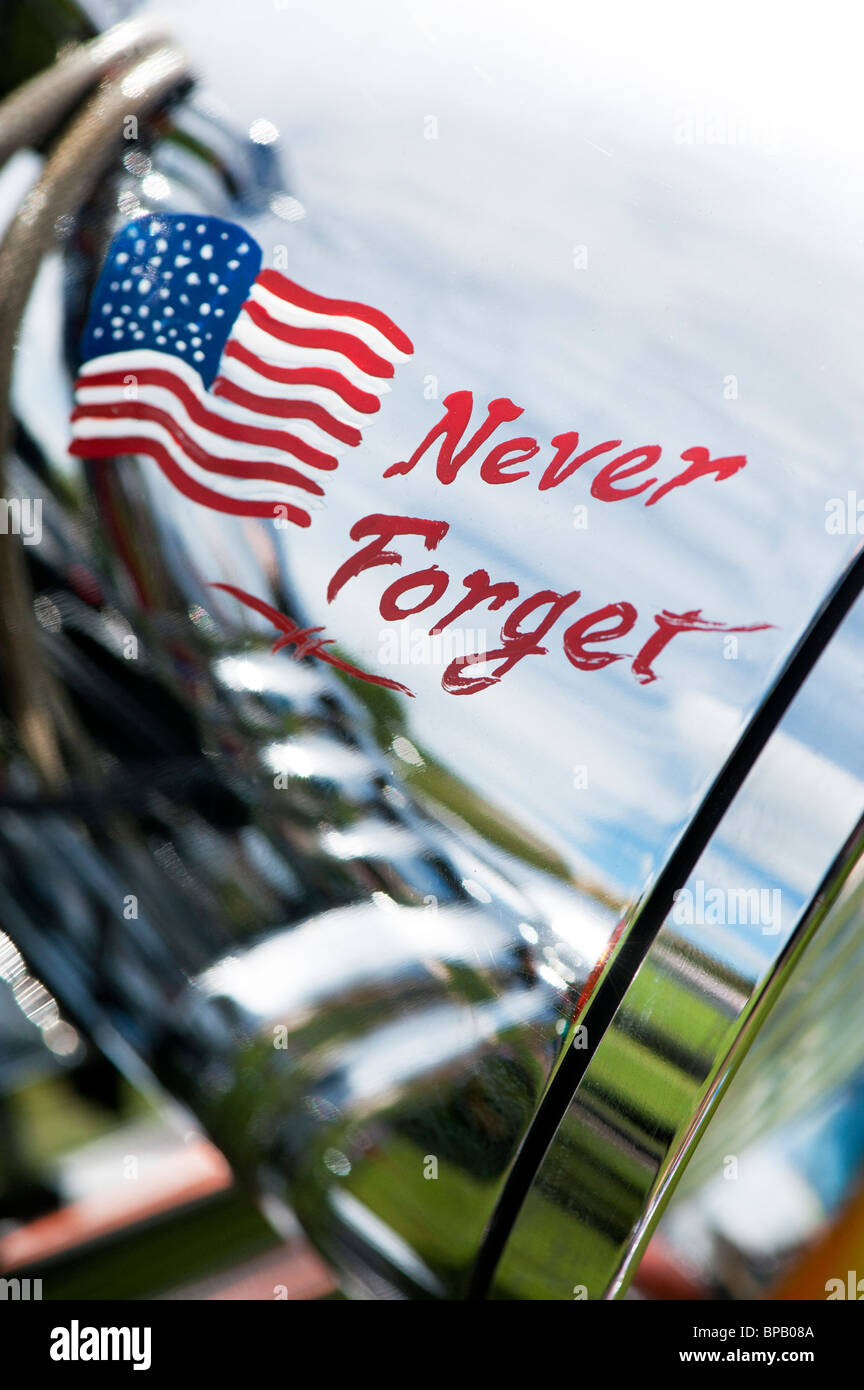 The words 'Never forget'  and an American flag painted on a Harley Davidson motorcycle chrome headlight - Stock Image