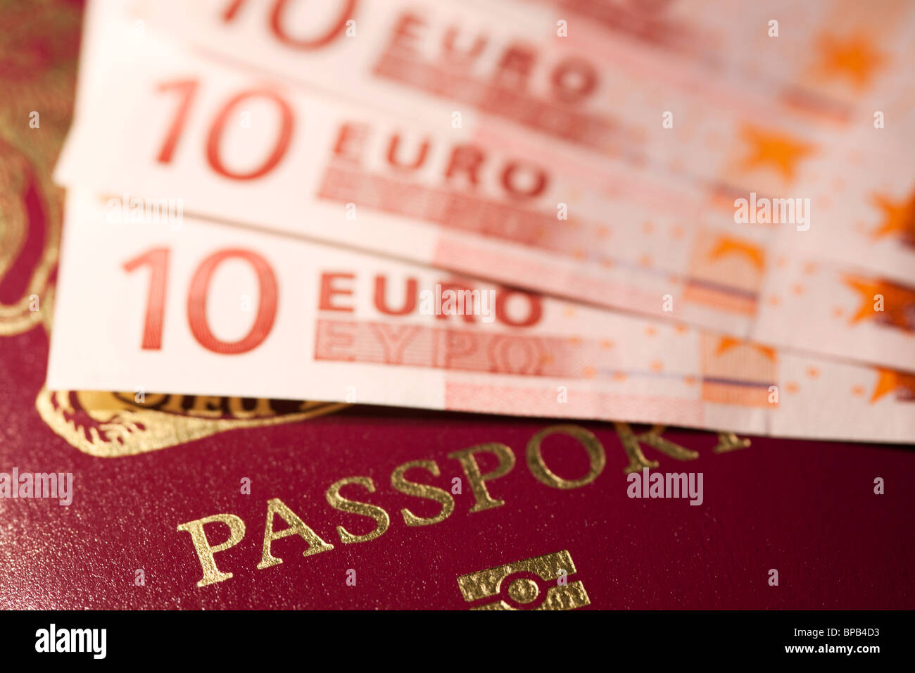 Passport with euros on top - Stock Image