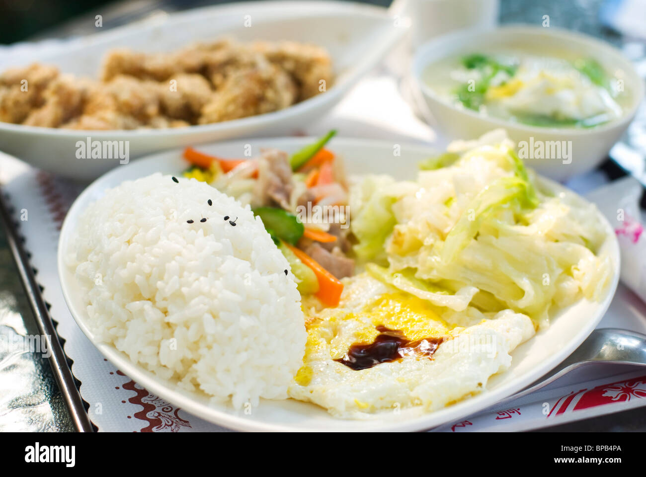 Delicious set of lunch. Chinese food with rice, egg, cabbage vegetable ,fried chicken and soup on the table. Stock Photo