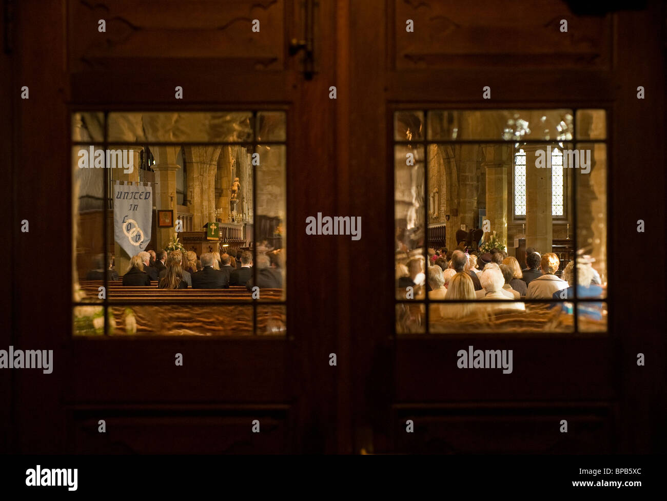 congegation in church viewed through windows - Stock Image