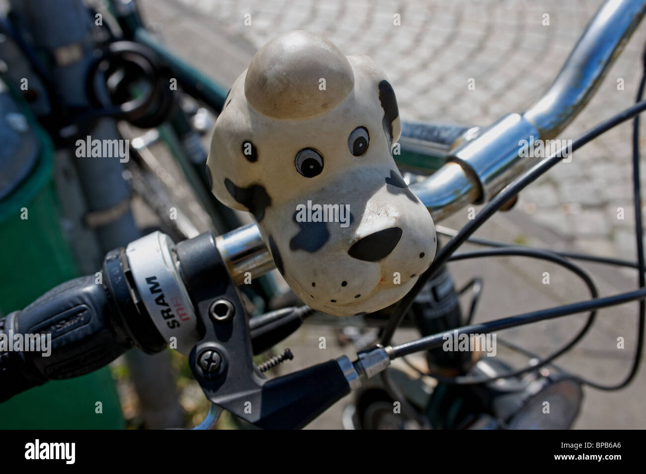 Dog shaped bicycle horn attached to handlebars - Stock Image