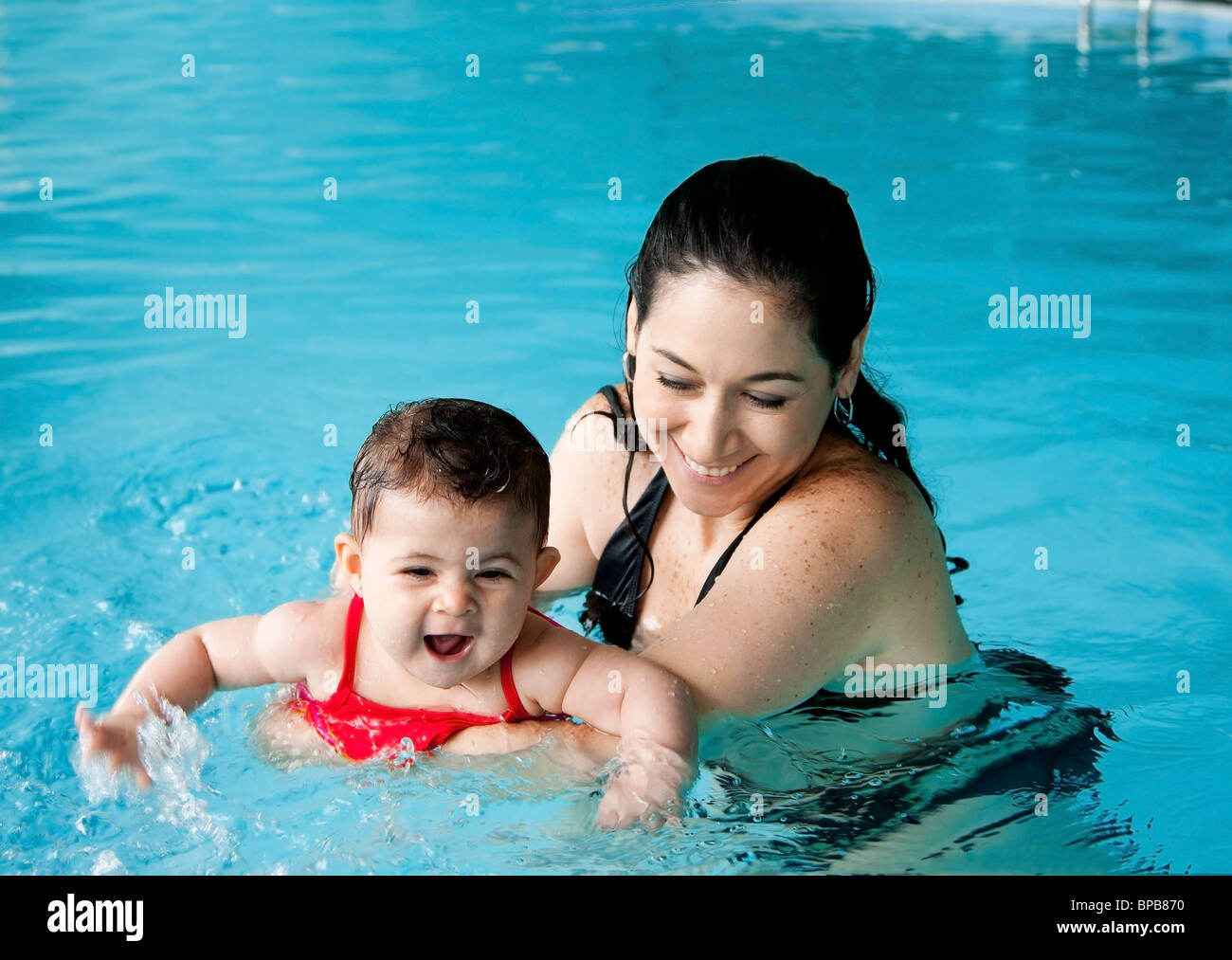Beautiful mother teaching cute baby girl how to swim in a swimming pool. Child having fun in water with mom. - Stock Image