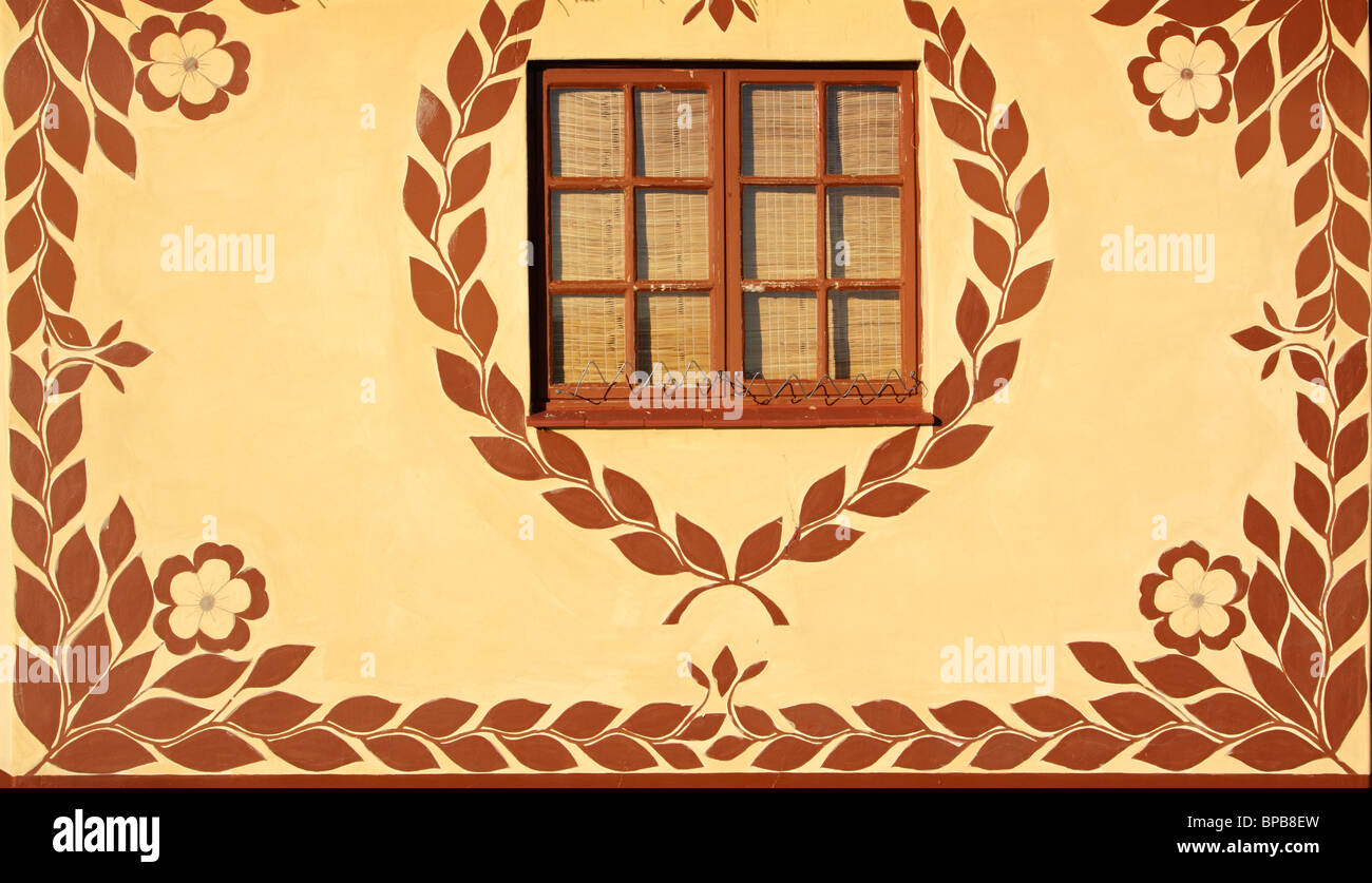 Wall of a hut decorated with traditional African motifs - Stock Image