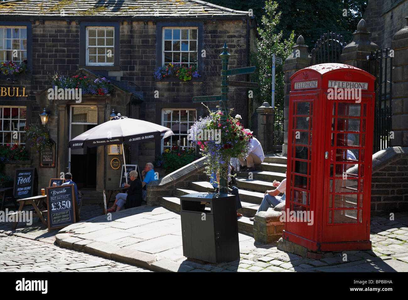 Visitors sat on church steps by the Black Bull pub on Main Street, Haworth, West Yorkshire, England, UK. - Stock Image