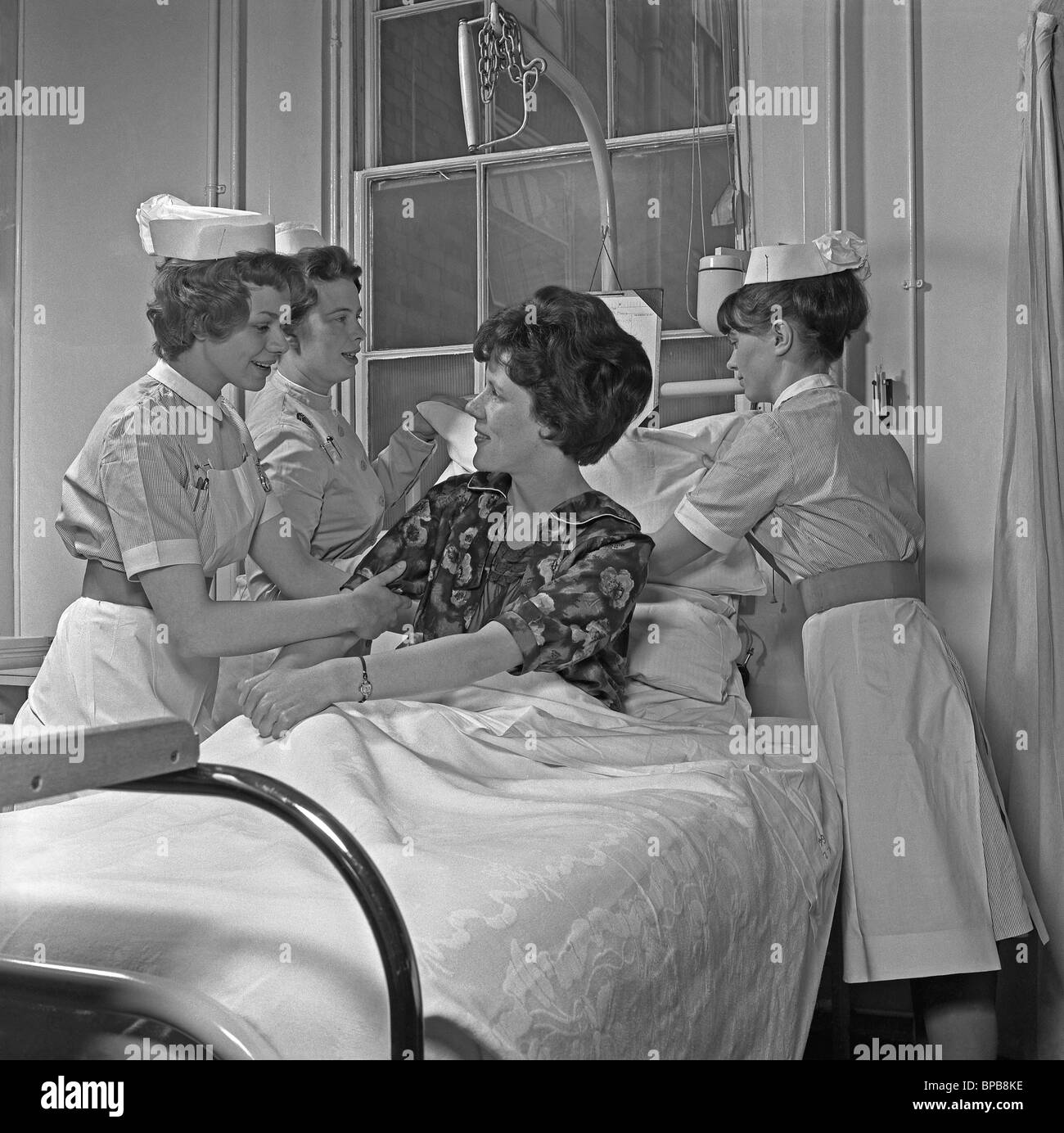 Hospital nurses gathered around a patient in bed adjusting her pillows in, c. 1960 - Stock Image