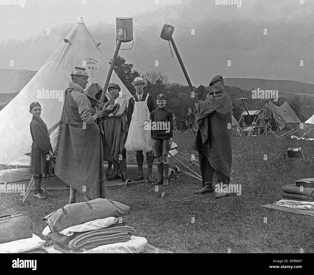 Unusual ritual involving boy scouts, a man wearing a colander on his head and another wearing a tutu at a scout - Stock Image