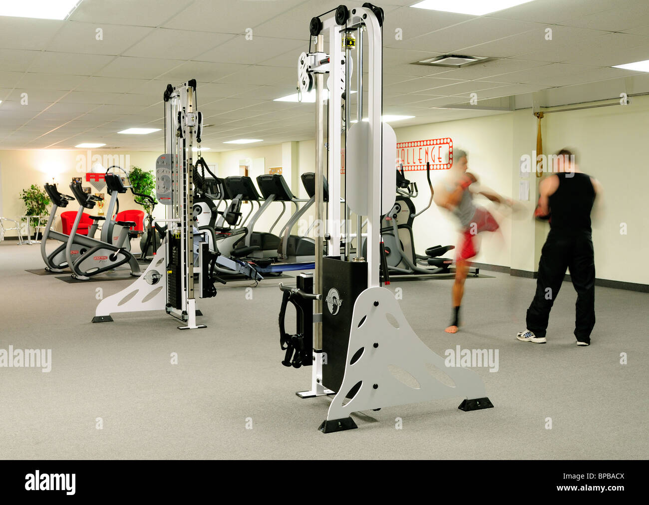 Interior Of A Commercial Gym With two People Kick Boxing - Stock Image