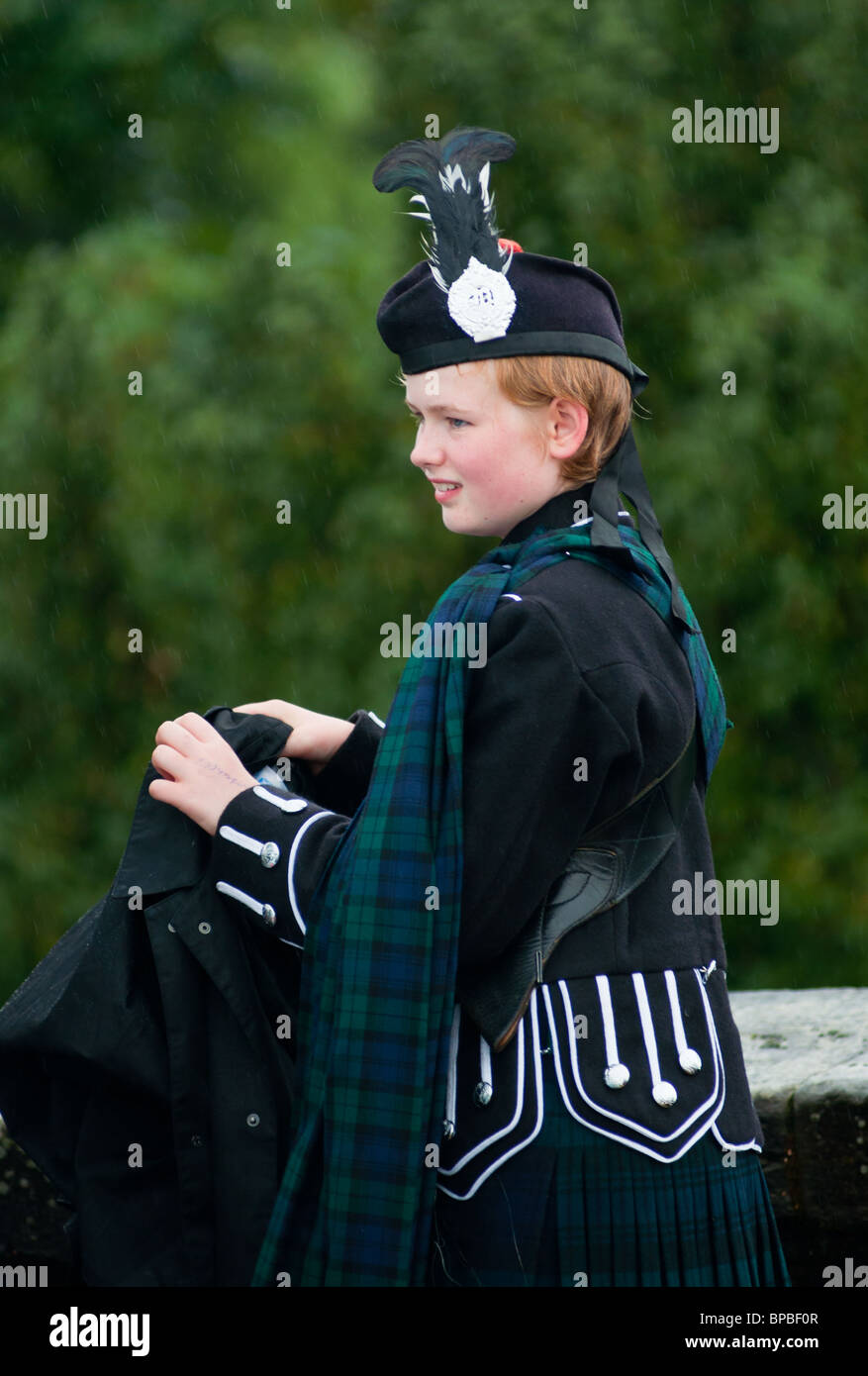 Scots girl with red hair and fair skin in traditional Scottish clothes. - Stock Image