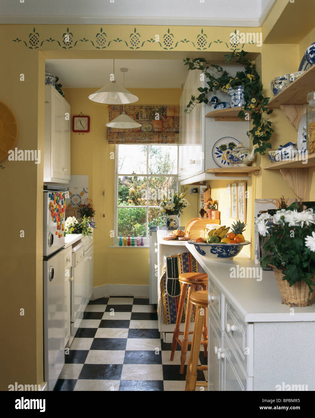 Black+white vinyl flooring in yellow galley kitchen with white ...