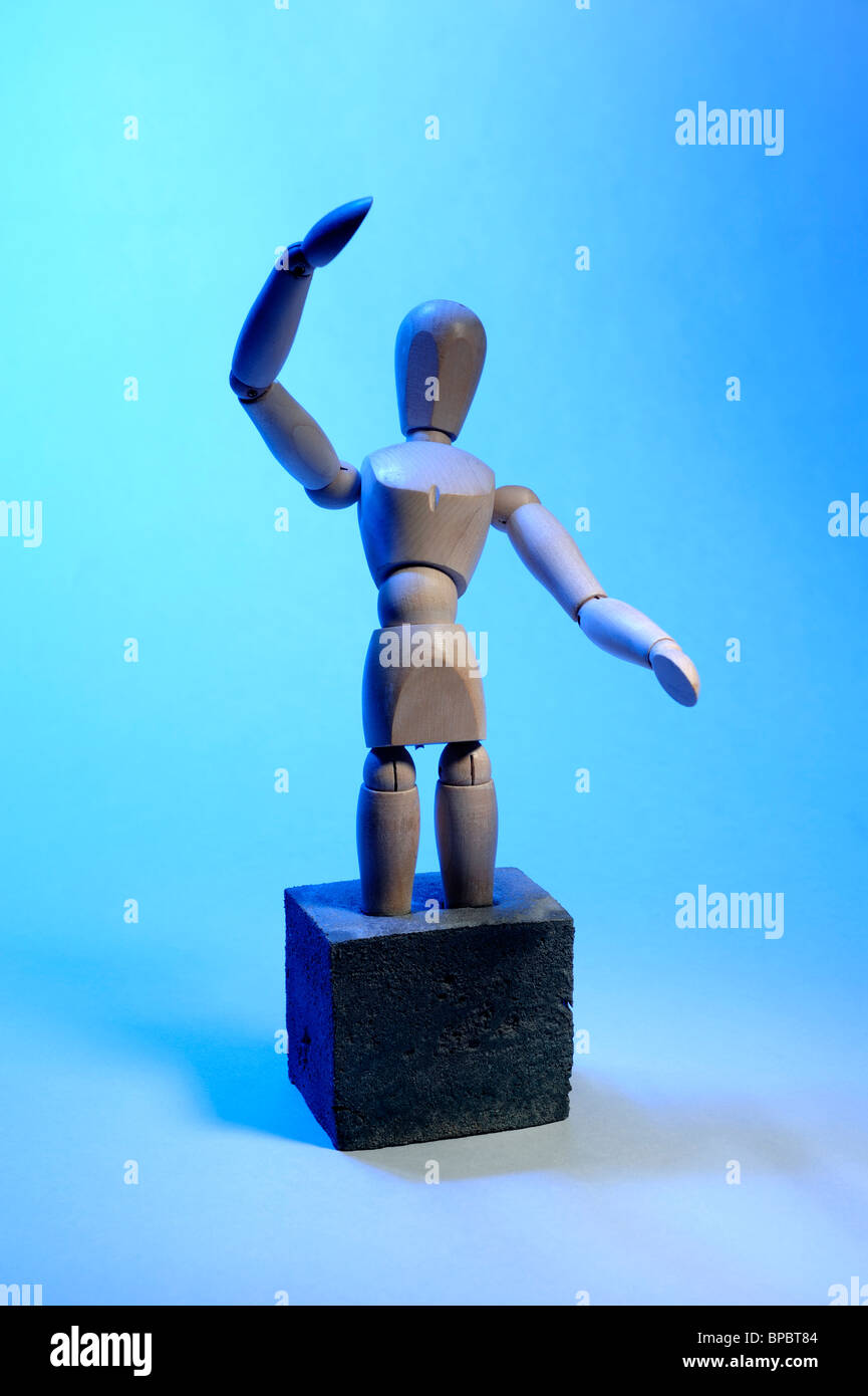 Wooden mannequin with feet set in concrete - Stock Image