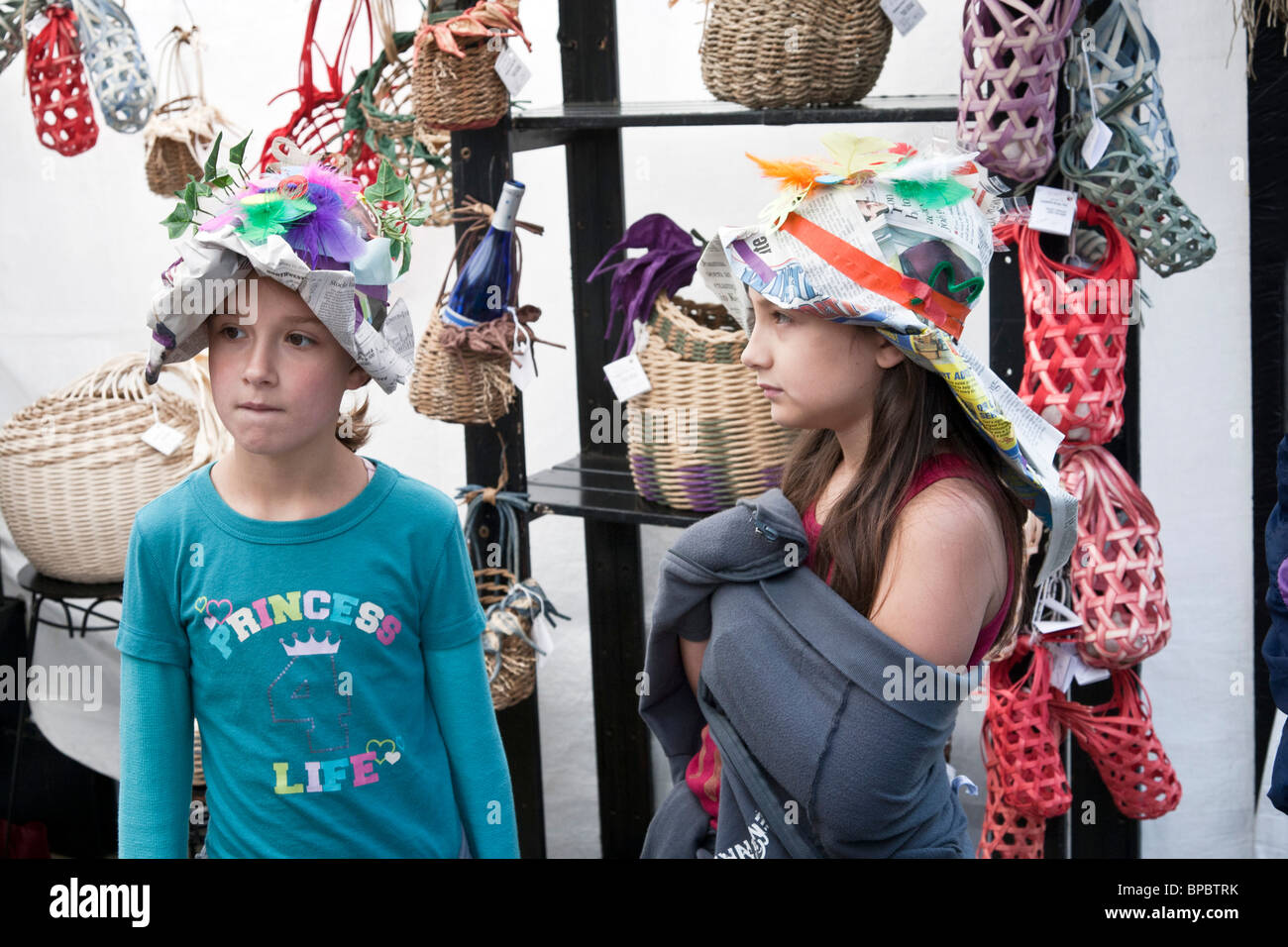 two little girls wearing fanciful decorated paper hats of their own invention at Everett waterfront art festival - Stock Image