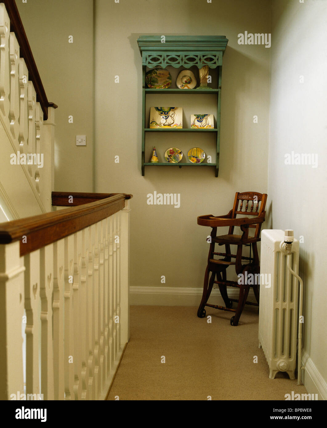 Small green shelves on wall above child's antique high chair on traditional  cream landing - Small Green Shelves On Wall Above Child's Antique High Chair On