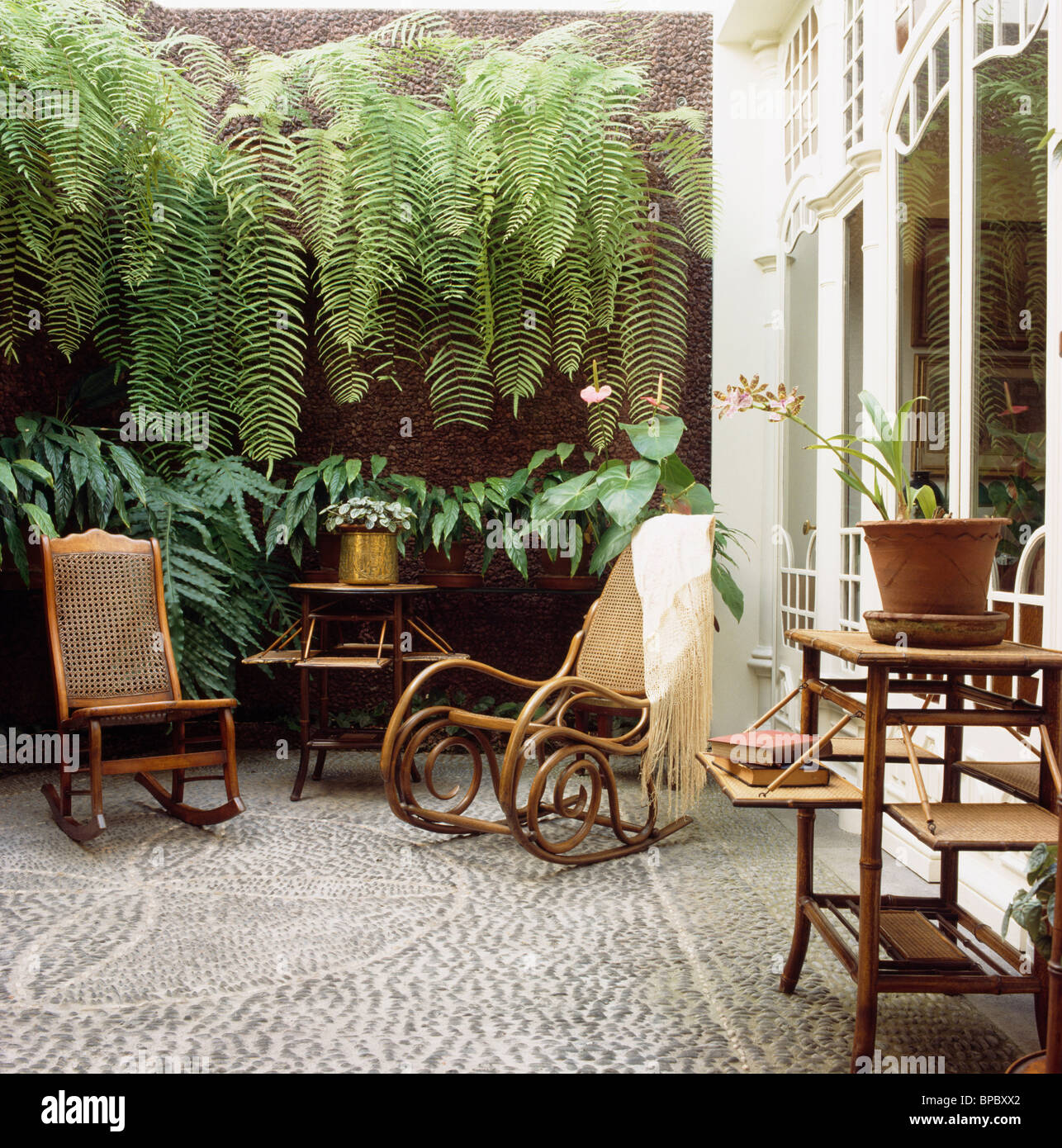 Antique Bentwood rocking chair and planter's chair on small townhouse  courtyard with pebble mosaic paving and lush green ferns - Antique Bentwood Rocking Chair And Planter's Chair On Small Stock